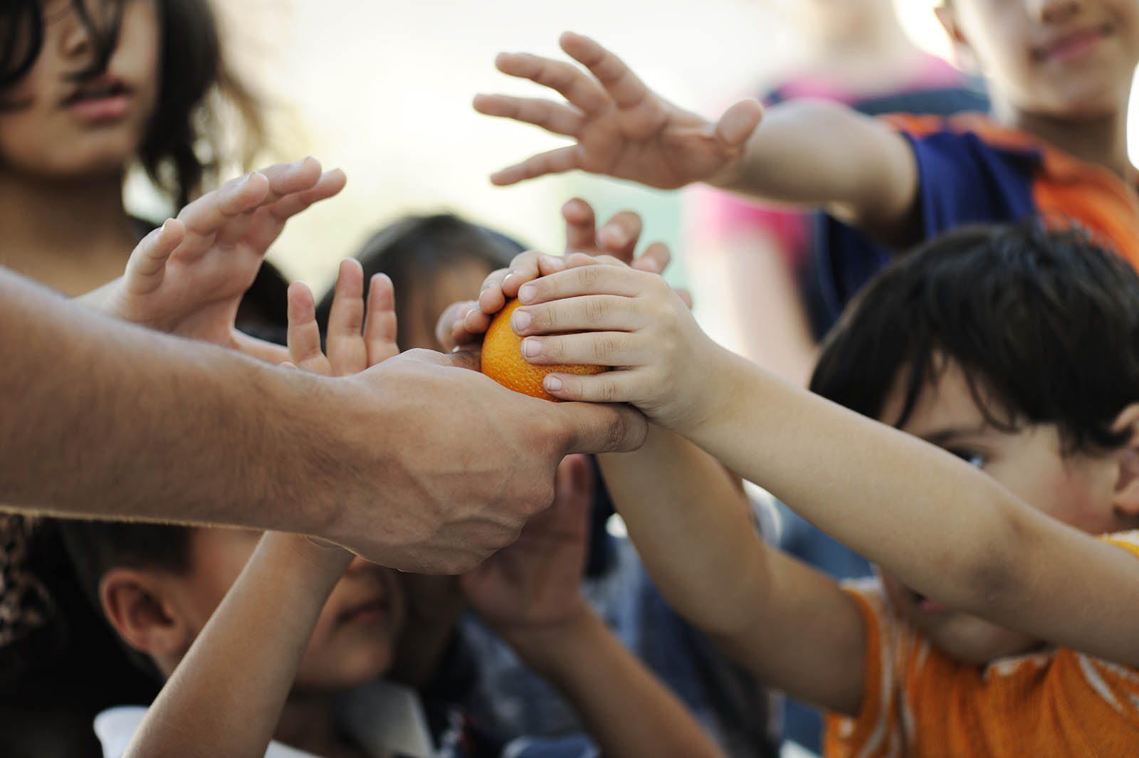 children in a group reaching up for an orange