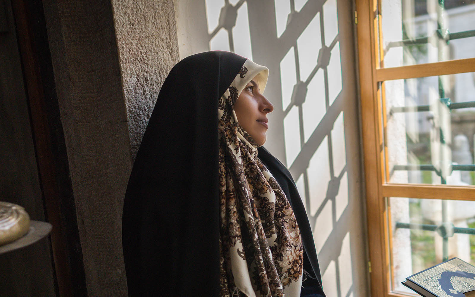 muslim woman looking out of the window